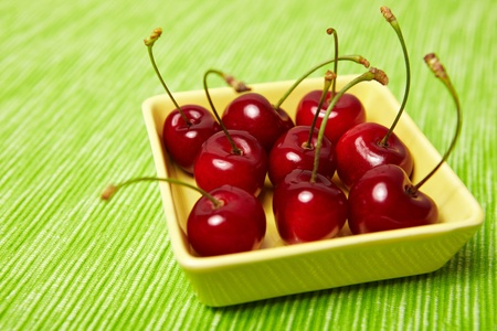Many red cherries for dessert on a green background