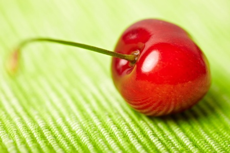 Single sweet cherry on a green tablecloth photo