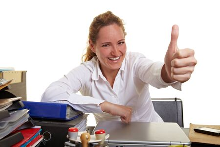 Smiling business woman at her desk holding thumbs up Stock Photo - 10175034