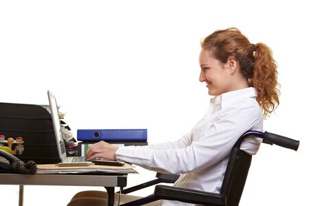 Smiling disabled woman in wheelchair working at desk with laptop photo