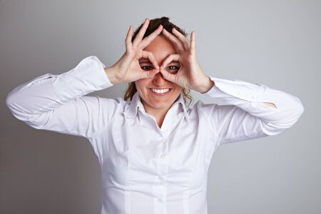 Happy business woman making circles with her fingers around her eyes photo