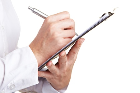 inspect: Hand filling out checklist on clipboard with a pen Stock Photo