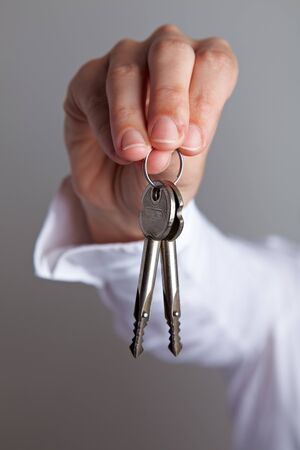 Hand holding two house keys on a key chain photo