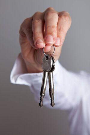 hand key: Hand holding two house keys on a key chain