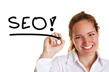 consultant: Smiling business woman writing the word SEO with pen