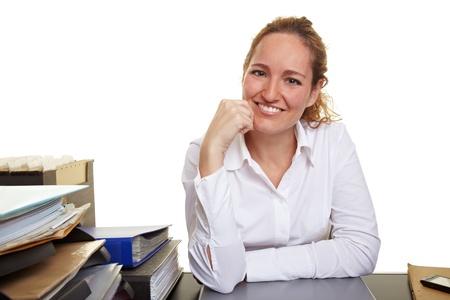 administracion de empresas: Retrato de una mujer joven y sonriente en el escritorio en la oficina Foto de archivo