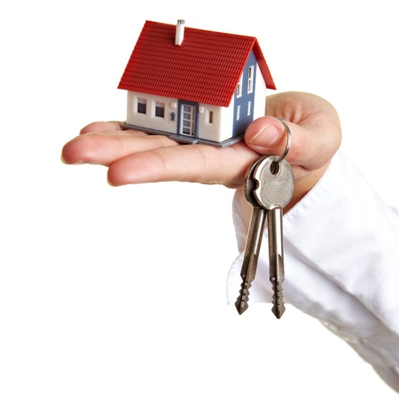 Hand holding small house and some keys photo