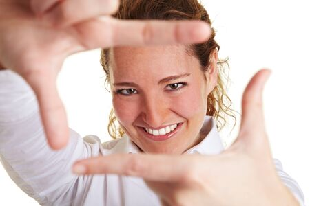 Business woman looking through finger frame made with her hands photo