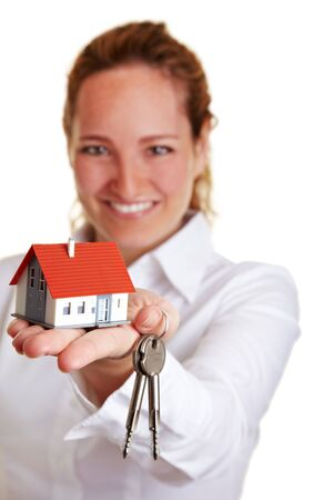 Businesswoman offering house keys and small house Stock Photo - 10174926