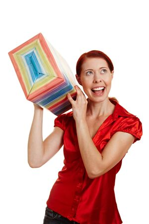 redhaired: Happy woman shaking a big christmas gift Stock Photo