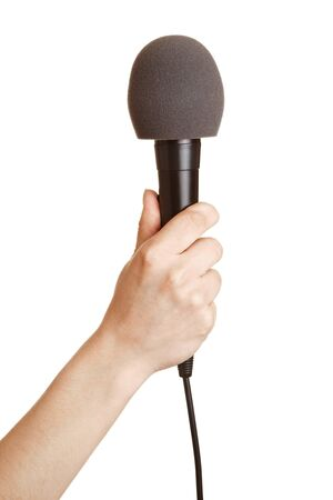 Hand holding a microphone with a windscreen up photo