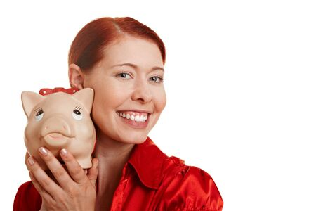 thrift box: Redhaired smiling young woman with piggy bank Stock Photo