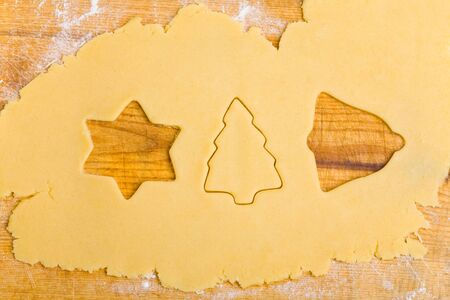 Different christmas cookie cuter shapes in cookie dough photo