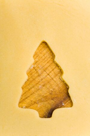 pastry cutter: Empty christmas tree shape in raw cookie dough