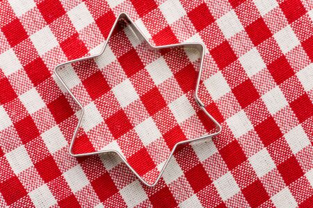 Star shaped cookie cutter on a red-white striped tablecloth photo