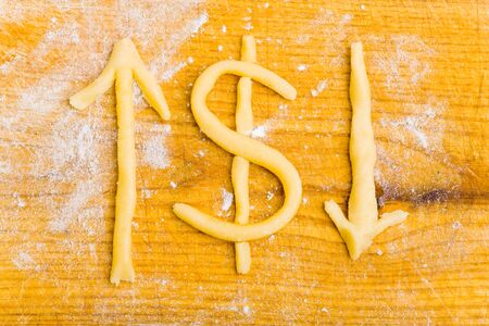 finanzen: Dollar sign and arrows made from cookie dough