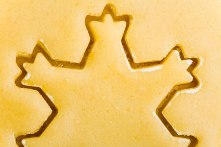 Close-up of snowflake cookie cutter on raw christmas cookie dough photo