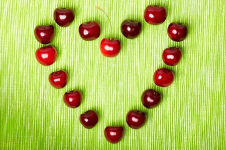 ripeness: Heart made of many red cherries on green background Stock Photo