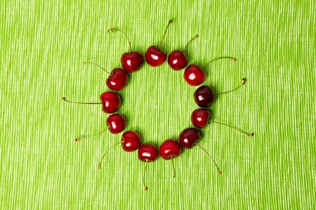 ripeness: Many red cherries in a circle on green background