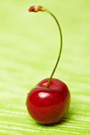 ripeness: Ripe cherry with stem on a green tablecloth