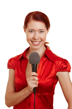 interviewing: Smiling redhaired reporter woman holding a microphone Stock Photo