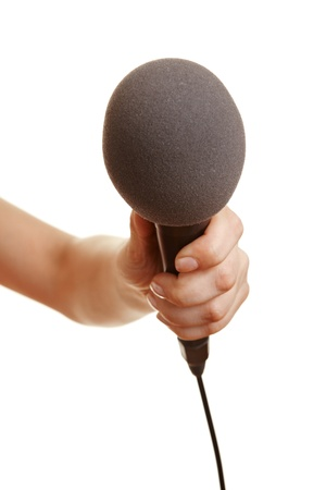 interviewing: Hand holding a microphone with a windscreen