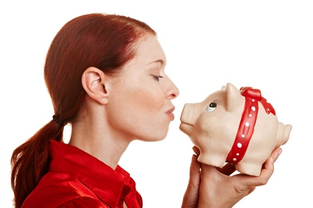 win money: Redhaired woman kissing a big piggy bank Stock Photo
