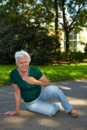 pangs: Senior donna seduta con corsa nel parco Archivio Fotografico