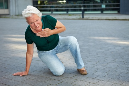 Senior woman getting heart attack in urban environment photo