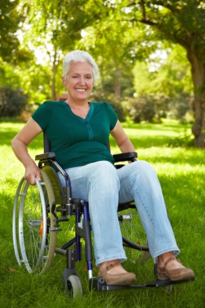 Happy elderly disabled woman in a wheelchair in a park photo