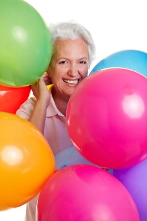 Happy senior woman celebrating with many balloons photo