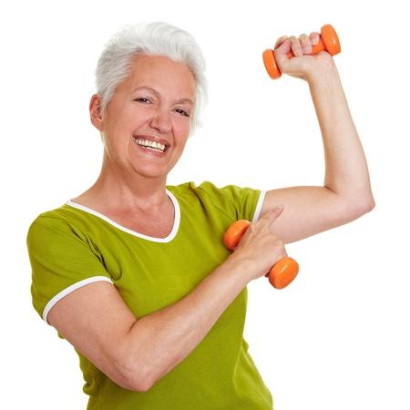 r�sistance: Femme senior heureuse avec halt�res montrant au large de ses muscles