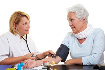 hypertension: Blood pressure measurement of senior woman at doctor Stock Photo