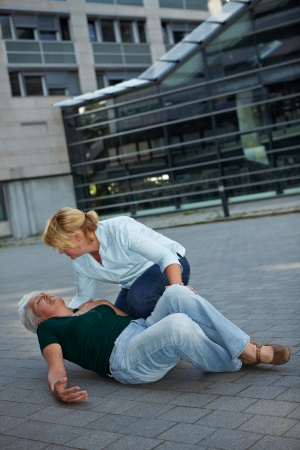 Passerby helping a senior woman with seizure photo