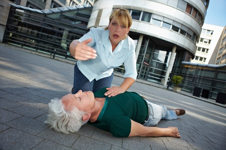 Passerby with unconscious senior woman asking for First Aid help photo
