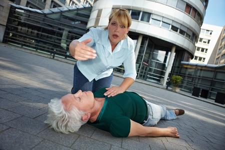 blackout: Voorbijganger met onbewuste senior vrouw vragen om Eerste Hulp te helpen Stockfoto