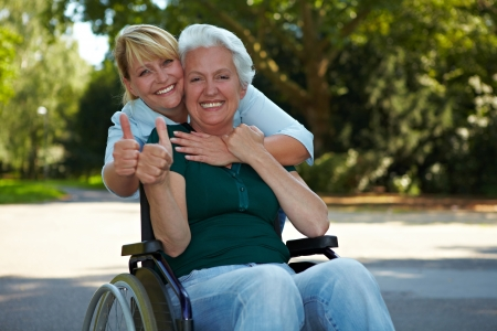 old people in care: Senior woman and nurse in holding thumbs up