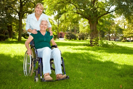 Happy disabled senior woman in wheelchair with nurse in nature