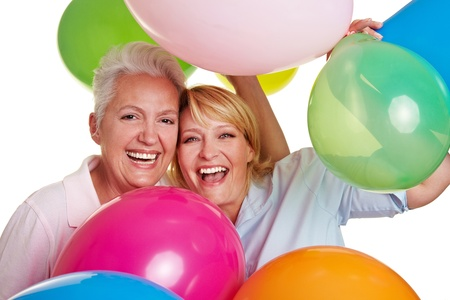 Two happy senior women cheering with many balloons photo