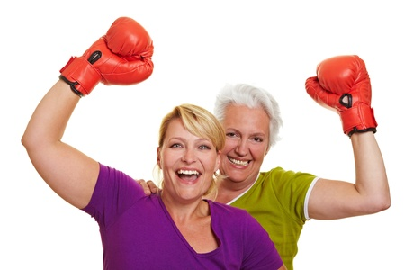 defense: Two happy senior women cheering with red boxing gloves