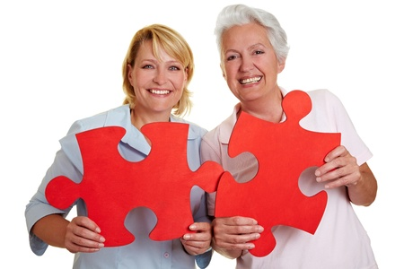 cutout old people: Two happy senior women holding jigsaw puzzle pieces