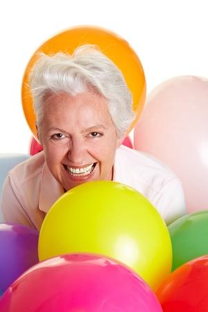 retirees: Happy senior woman having fun with colorful balloons Stock Photo