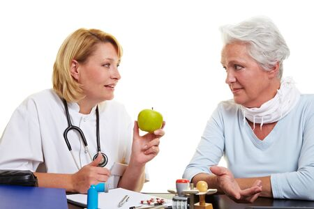 recommending: Doctor recommending a green apple to senior woman