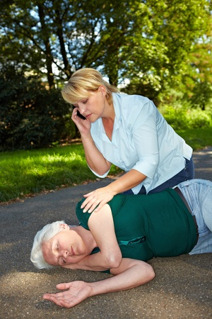 Passerby near helpless senior woman calling emergency ambulance photo