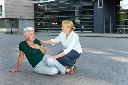 convulsion: Ayudar a los transe�ntes d�bil mujer mayor con un accidente cerebrovascular Foto de archivo