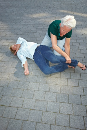 recovery position: Senior woman using recovery position on unconscious woman Stock Photo