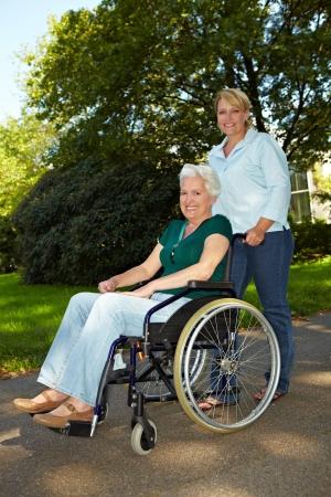 rollstuhl: L�chelnd Krankenschwester treibende �ltere Frau im Rollstuhl durch den Park