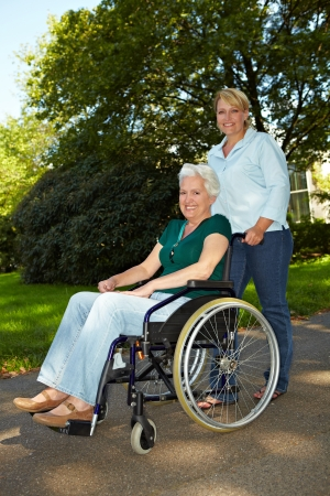 mobility nursing: Smiling nurse driving senior woman in wheelchair through park Stock Photo