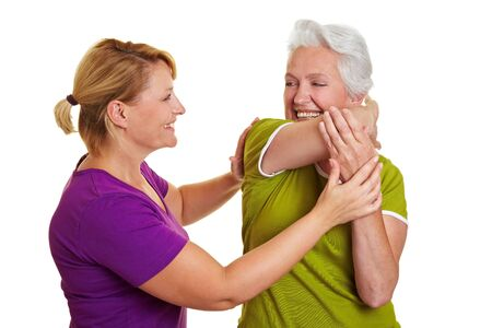 rehab: Senior woman exercising with personal fitness trainer Stock Photo