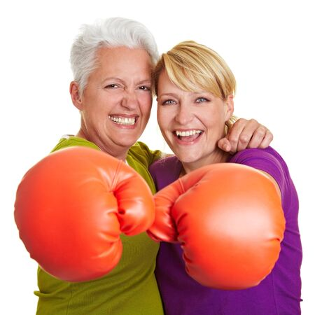 Two happy senior women boxing with red boxing gloves photo